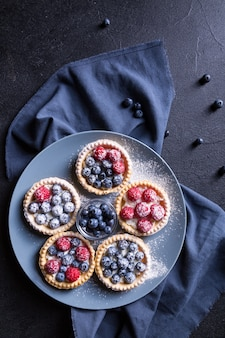 Вкусный десерт со свежей черникой и малиной на большой серой тарелке. черный фон.