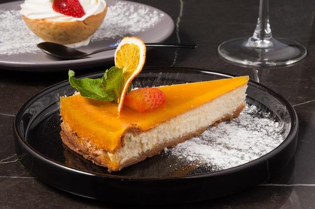 黒いプレートにオレンジ色のチーズケーキが入ったおいしいデザート