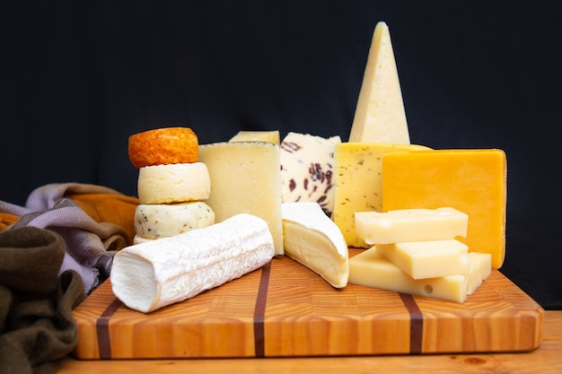 Tasty different cheeses laying on wooden board