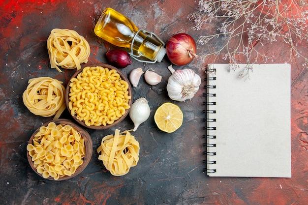 Вкусное приготовление обеда с сырыми макаронами в различных формах и чесноком, упавшим маслом, чесноком, лимоном и блокнотом на смешанном цветном фоне