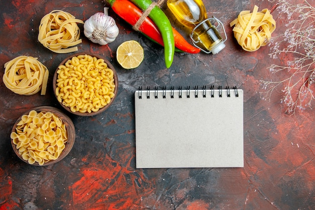 さまざまな形の未調理のパスタとニンニクの落ちたオイルボトルガーリックレモンと混合色の背景のノートブックでおいしい夕食の準備