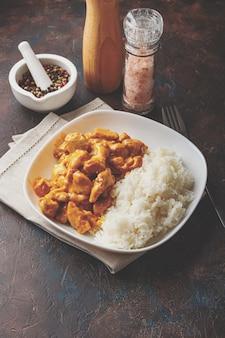 Вкусный ужин с курицей в соусе карри из кокосового молока с рисом в белом блюде, вид сверху. азиатский стиль.