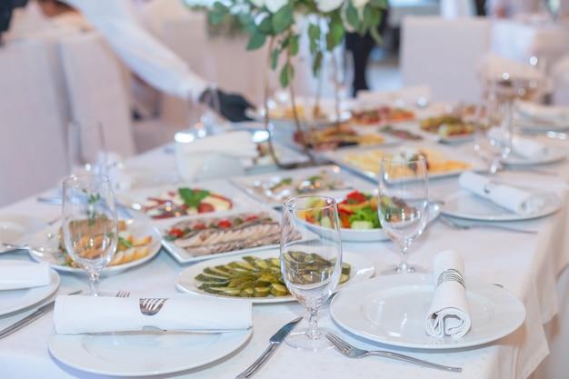 豪華なレストランで提供される白い宴会テーブルでおいしい料理。
