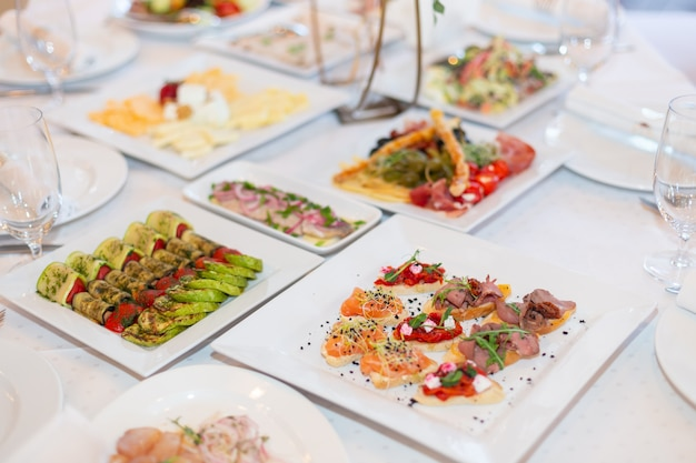 Tasty dishes on a served white banquet table in a luxury restaurant.