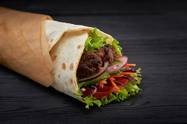 Tasty doner kebabs with fresh salad trimmings and shaved roasted meat served in tortilla wraps on brown paper as a takeaway snack Premium Photo
