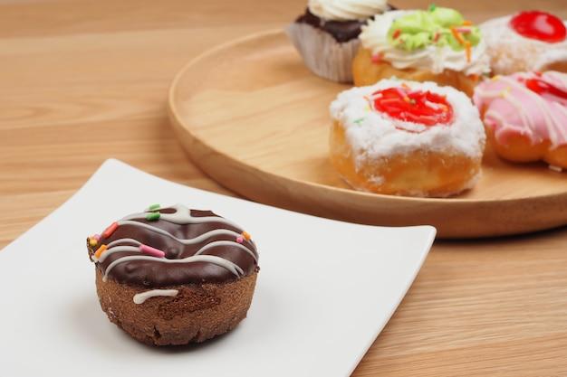 茶色の木製テーブルの背景、パン屋の上の白い皿のおいしいドーナツ