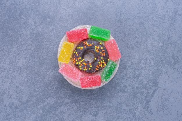 Вкусный пончик с мармеладными конфетами на серой поверхности