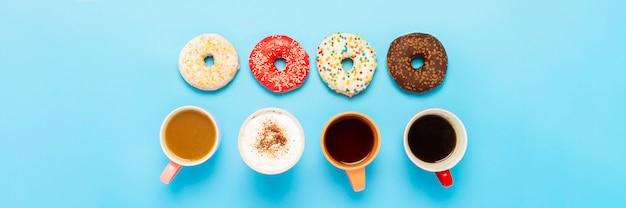 Вкусные пончики и чашки с горячими напитками, кофе, капучино, чай на синей поверхности. концепция сладости, хлебобулочные изделия, выпечка, кафе, встречи, друзья, дружная команда. , плоская планировка, вид сверху