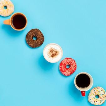 Вкусные пончики и чашки с горячими напитками, кофе, капучино, чай на синей поверхности. концепция сладости, хлебобулочные изделия, выпечка, кафе, встречи, друзья, дружная команда. площадь. плоская планировка, вид сверху