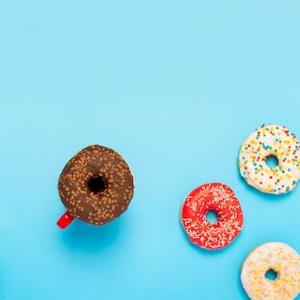 Вкусные пончики и чашки с горячими напитками на синей поверхности. концепция сладости, хлебобулочные изделия, выпечка, кафе. площадь. плоская планировка, вид сверху