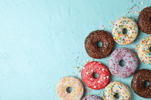 Tasty donuts on blue background, top view