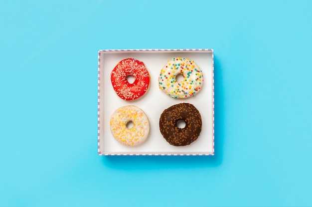Tasty donuts in a box on a blue surface. concept of sweets, bakery, pastries, coffee shop. . flat lay, top view