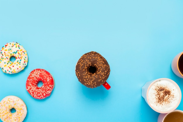 Tasty donuts and cups with hot drinks on a blue surface. concept of sweets, bakery, pastries, coffee shop. square. flat lay, top view
