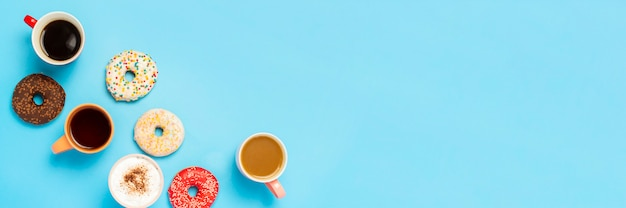 Tasty donuts and cups with hot drinks, coffee, cappuccino, tea on a blue surface. concept of sweets, bakery, pastries, coffee shop, meeting, friends, friendly team. . flat lay, top view