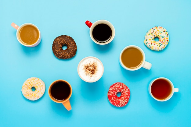 Tasty donuts and cups with hot drinks, coffee, cappuccino, tea on a blue surface. concept of sweets, bakery, pastries, coffee shop, meeting, friends, friendly team. flat lay, top view