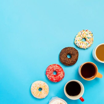 Tasty donuts and cups with hot drinks, coffee, cappuccino, tea on a blue surface. concept of sweets, bakery, pastries, coffee shop, meeting, friends, friendly team. the square. flat lay, top view
