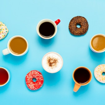 Tasty donuts and cups with hot drinks, coffee, cappuccino, tea on a blue surface. concept of sweets, bakery, pastries, coffee shop, meeting, friends, friendly team. square. flat lay, top view