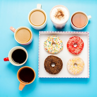 Tasty donuts and cups with hot drinks, coffee, cappuccino, tea on a blue surface.
