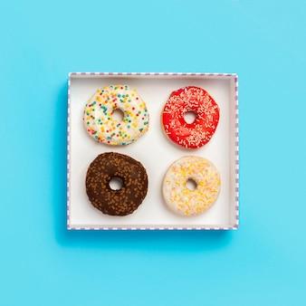 Вкусные пончики в коробке на синем. концепция сладостей, хлебобулочных, кондитерских изделий, кафе
