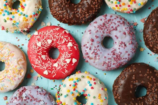 Вкусные пончики на синем фоне, вид сверху
