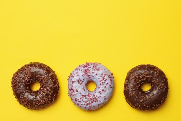 Вкусные пончики на желтом фоне, место для текста