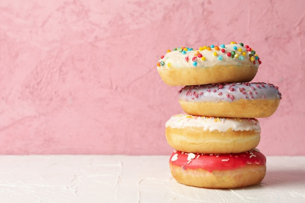 Tasty donuts on white table against pink background