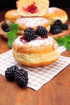Вкусные пончики с ягодами на деревянном столе