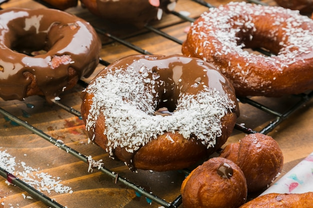 Tasty donuts with chocolate syrup and grated coconut on baking tray