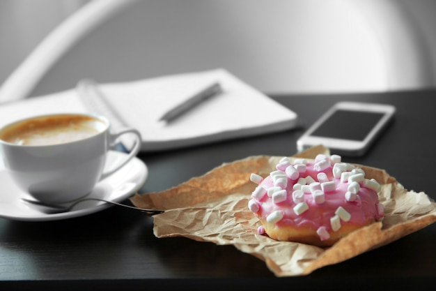 Tasty doughnut and cup of coffee on office table