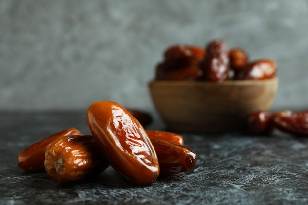 Tasty dried dates on black smokey table, close up