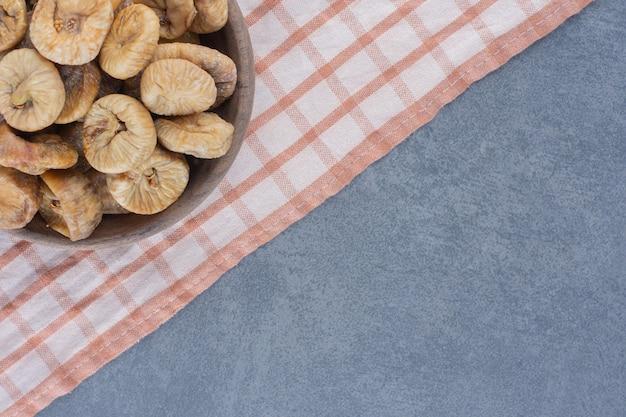 大理石の背景に、タオルの上にボウルにおいしいドライフルーツ。