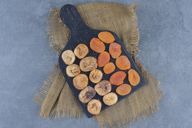 대리석 배경에 삼발이에 보드에 맛있는 말린 과일.