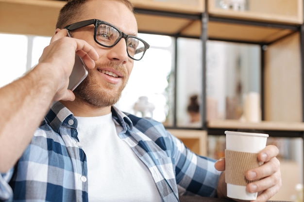Tasty drink. positive intelligent good looking man holding a plastic cup with coffee and enjoying his drink while having a conversation via cell phone