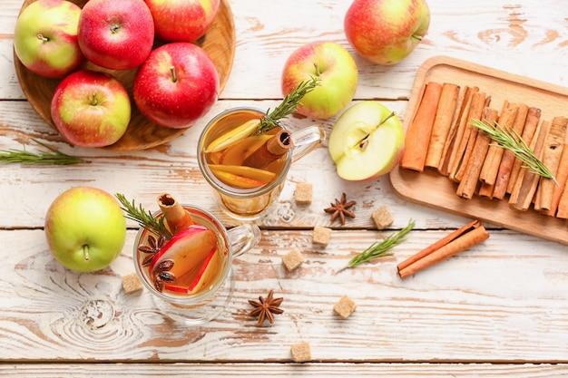木製の背景にカップのスパイスとリンゴのスライスとおいしい飲み物