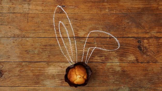 木製の表面に耳を持つおいしいイースターカップケーキ