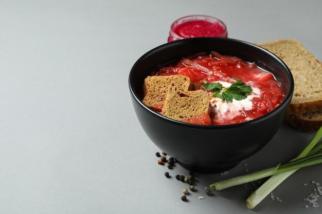 Вкусная еда с борщом и ингредиентами на сером столе