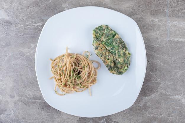Cotoletta saporita dell'uovo con i verdi e gli spaghetti sul piatto bianco.