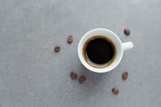 Tasty espresso in cup with coffee beans. view from above. concrete table.