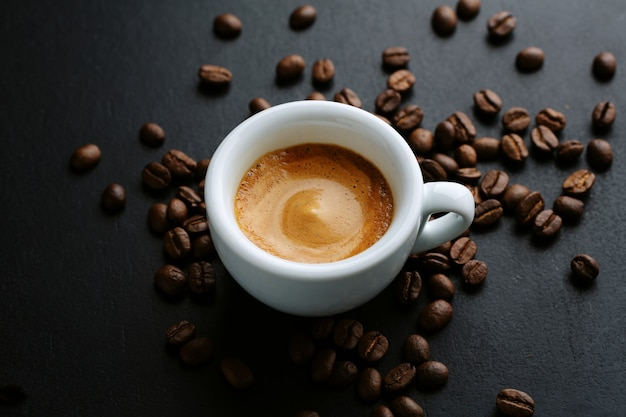 Tasty espresso served in cup with coffee beans around and spoon. closeup. dark background.