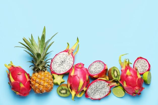 Вкусные экзотические фрукты на синем, вид сверху