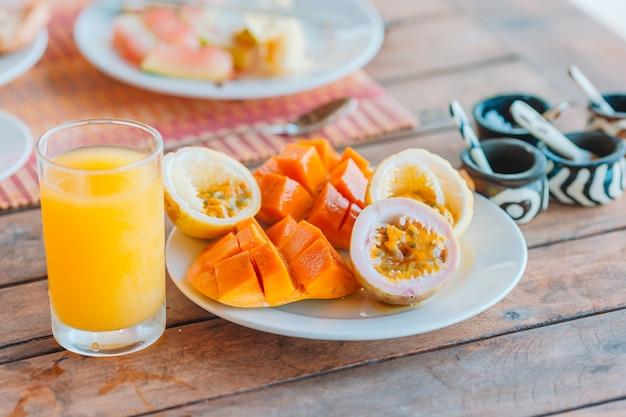 Вкусные экзотические фрукты - спелые маракуйи, манго на завтрак в ресторане на открытом воздухе