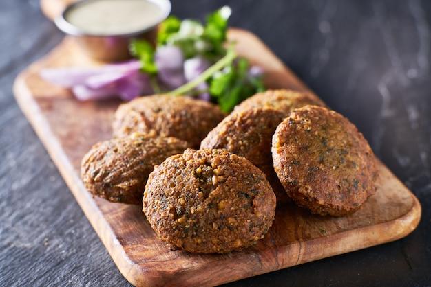 Tasty falafel pieces on wooden bread board