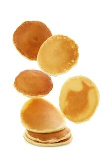 Tasty falling pancakes isolated on white background