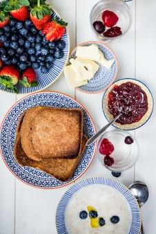 Tasty family breakfast with toasts, porridge, berries