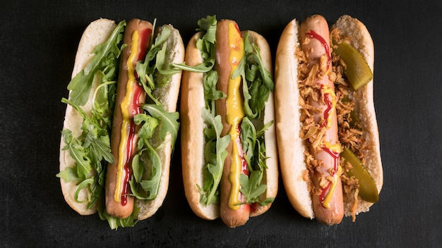 Tasty fast-food hot dog flat lay