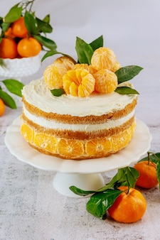 Tasty festive cake with peeled mandarins and green leaves.