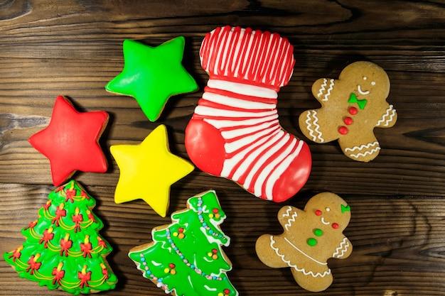 Вкусные праздничные рождественские пряники в форме елки, пряничного человечка, звезды и рождественского чулка на деревянном столе. вид сверху