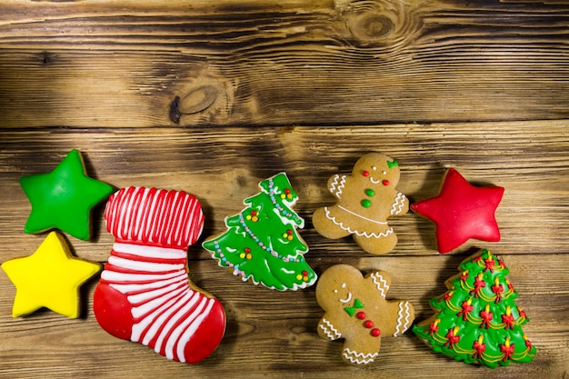 Tasty festive christmas gingerbread cookies in the shape of christmas tree, gingerbread man, star and christmas sock on wooden table. top view