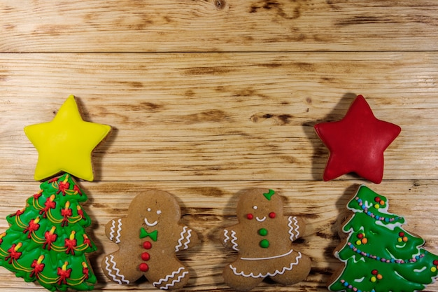 Tasty festive christmas gingerbread cookies in the shape of christmas tree, gingerbread men and stars on wooden table. top view