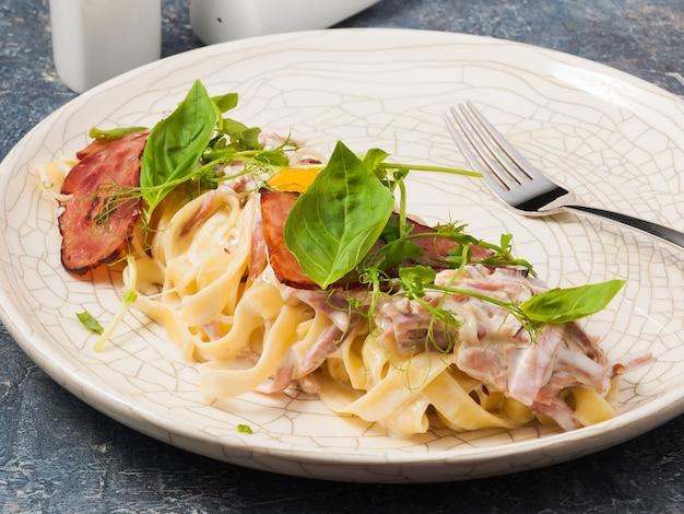 바질로 장식 된 가벼운 접시에 맛있는 페투치니 까르보나라 파스타